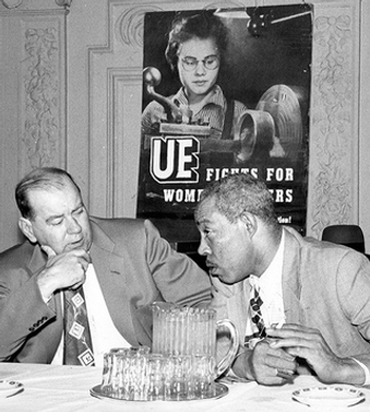 A black and white photo of Ernest Thompson at a table leaning forward in conversation with a man, in front of a union poster.