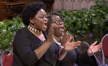 Two women - Yara Allen and Reverend Shyrl Uzzell smiling, singing, and clapping.