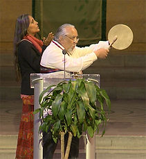 Chief Dwaine Perry of the Ramapough Lenape strikes a small hand drum behind a podium.