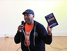 Dominic Moulden speaks into a microphone smiling while holding up a book.