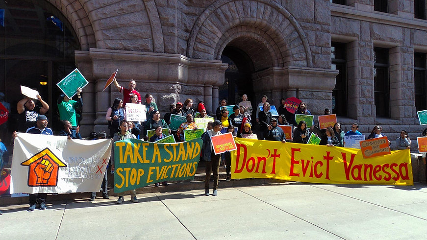 A diverse group of people on the steps of a municipal building protesting against evictions with large colorful banners.