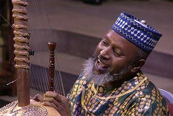 Salieu Suso plays the kora while singing and smiling.
