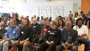 A diverse audience of people sitting with their eyes closed in reflection.