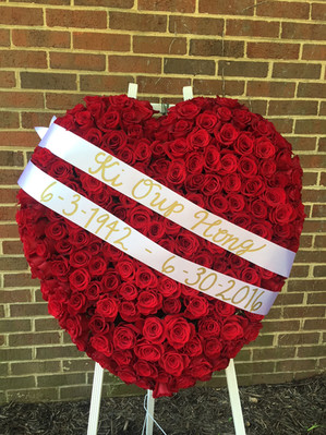red rose heart funeral stand with white ribbon
