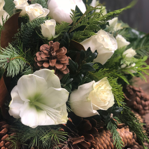 Evergreen Christmas arrangement with pinecones and white amaryllis