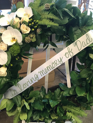 green funeral wreath with orchids and white ribbon
