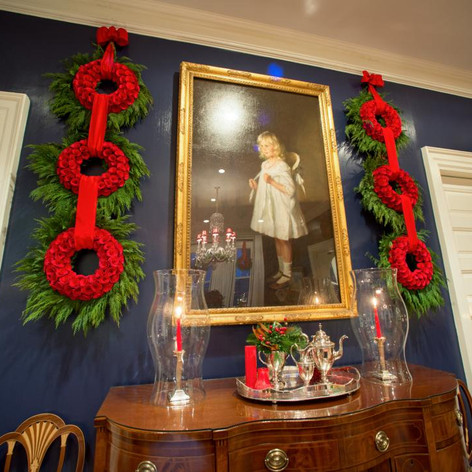Triple hanging evergreen wreaths with red ribbon; Photo Credit: HGTV
