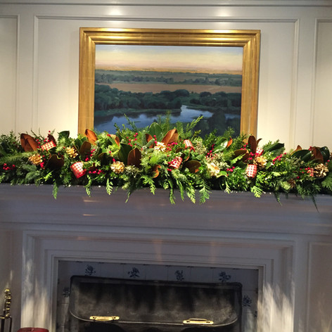 Evergreen fireplace Christmas garland with gold pinecones, ribbon loops and magnolia leaves