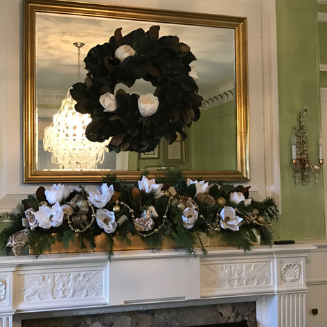 White and gold fireplace decor and mirror wreath with evergreens and magnolia