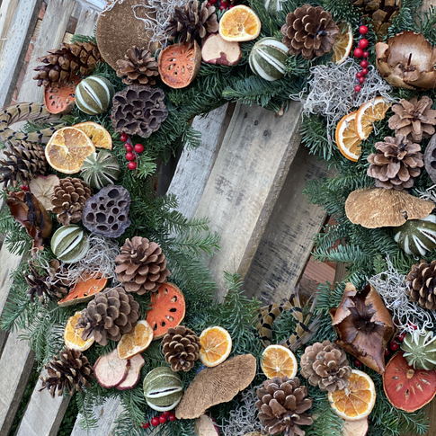 Evergreen Christmas wreath with pinecones, dried fruit slices and dried seed pods