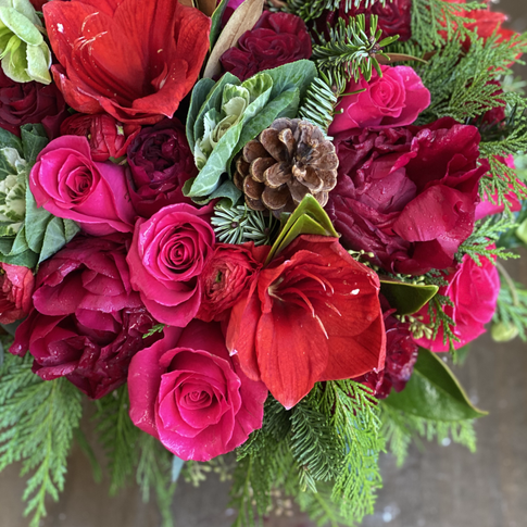 Evergreen centerpice with red roses, amaryllis, and pinecones