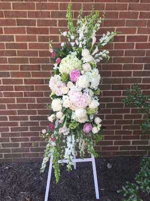 pastel funeral spray with white easel