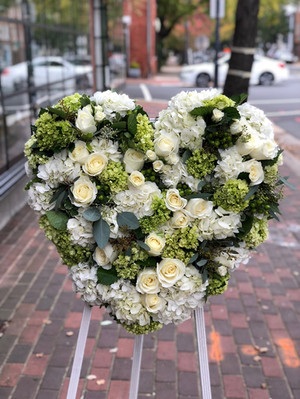 green and white heart sympathy arrangement on white easel