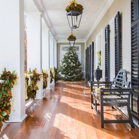 White and gold outdoor porch Christmas tree and magnolia porch railing swag