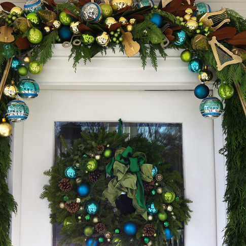 Blue and green front door garland and wreath with ornaments and magnolia leaves