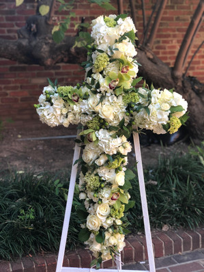 white and green cross funeral arrangement