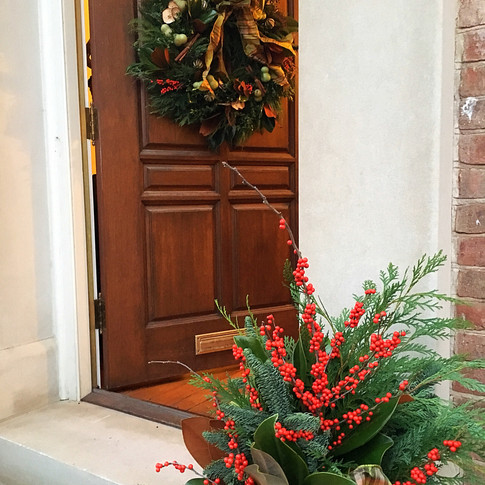 Red and gold outdoor Christmas planter urn with evergreens and berries, coordinating door wreath