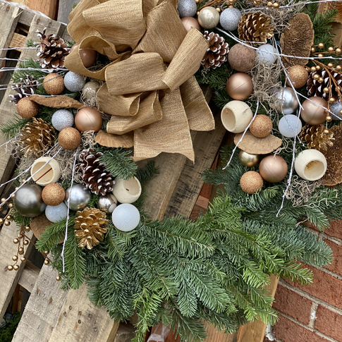 Evergreen wreath with copper ornaments, dried pods, branches, pinecones, and a burlap bow