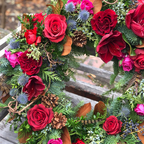 Christmas wreath with berry toned roses and blue thistle accents
