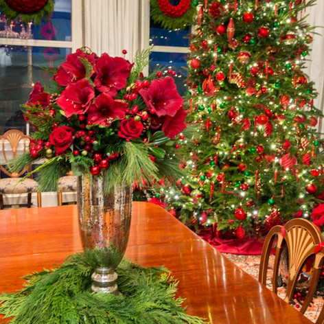 Red Christmas tree decorations and evergreen table arrangement with red amaryllis; Photo Credit: HGTV