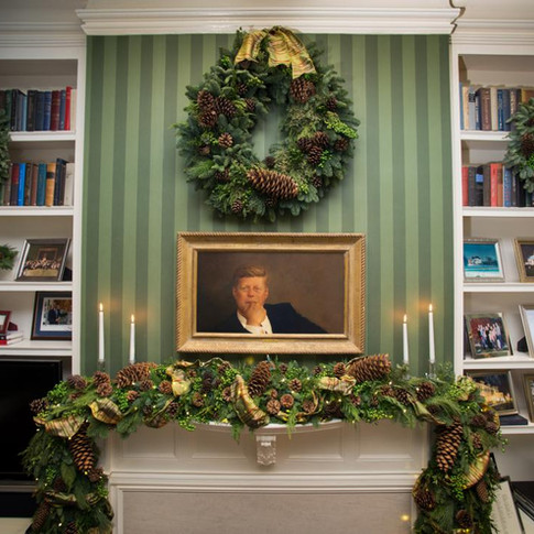 Classic evergreen fireplace garland and wreath with pinecones and gold ribbon; Photo Credit: HGTV