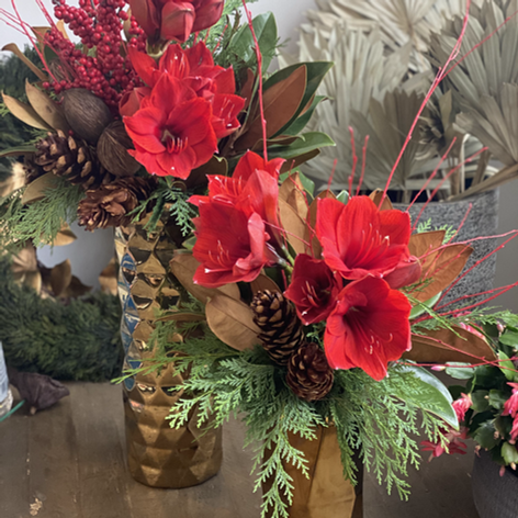 Gold Christmas vases filles with evergreens, amaryllis and red berry accents
