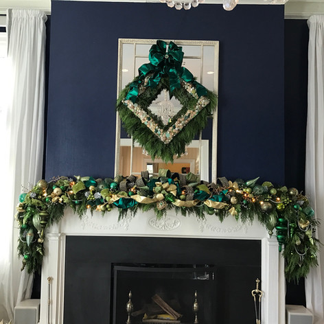 Evergreen mantle garland and mirror wreath with teal and gold ornaments and ribbon accents