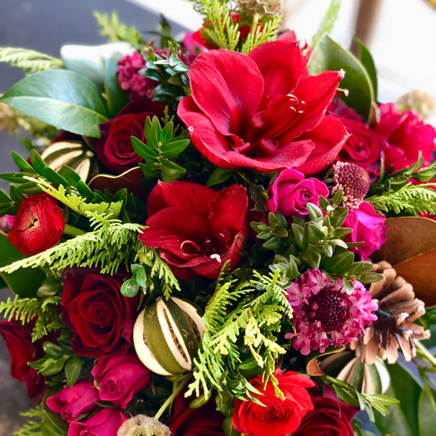 Evergreen Christmas arrangment with red amaryllis and berry accents