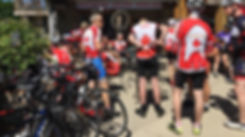 A background photo of group of Ancaster Velo riders stopped at a rest stop