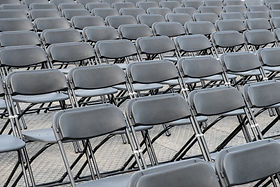 rows of empty chairs - black folding cha