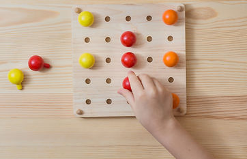The child is playing with wooden colorfu
