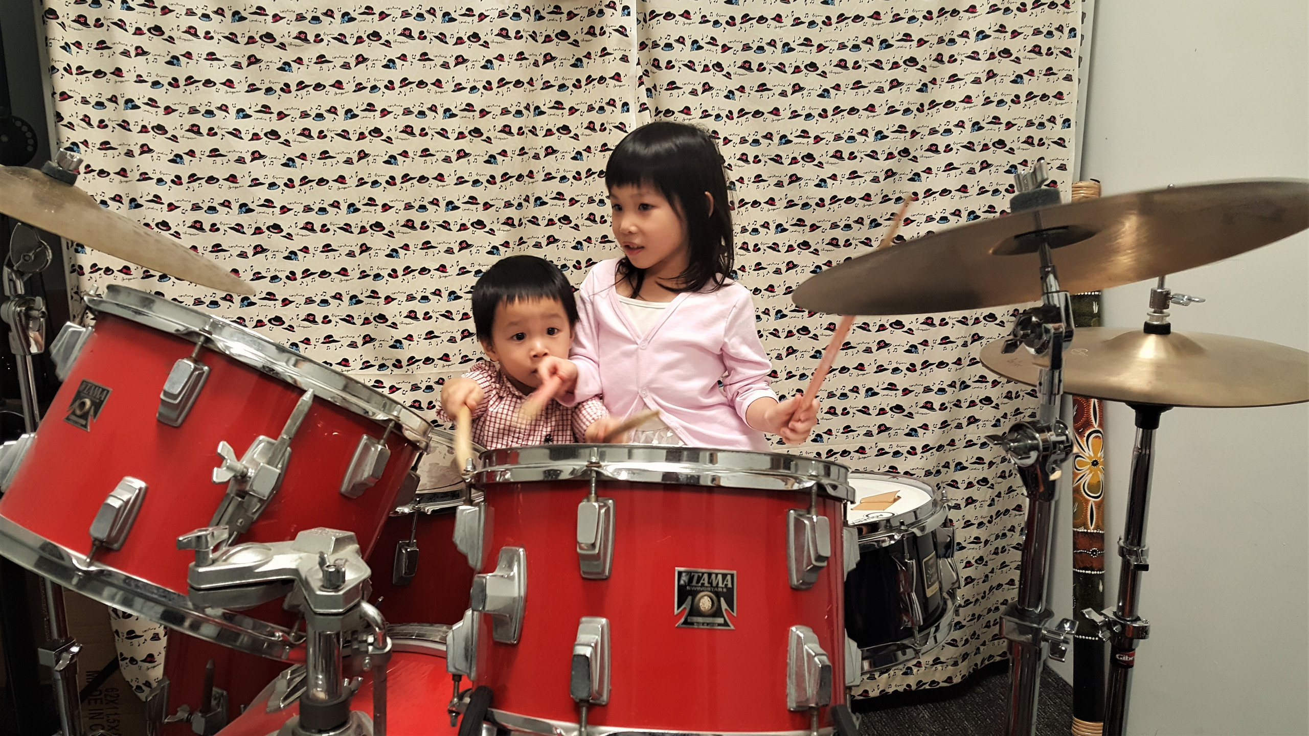 The lil' duo having fun on the drums