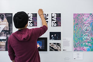 Student pins up graphic posters