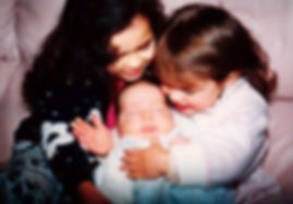 Sisters cuddling new baby