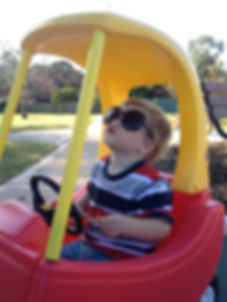 toddler posing in play car