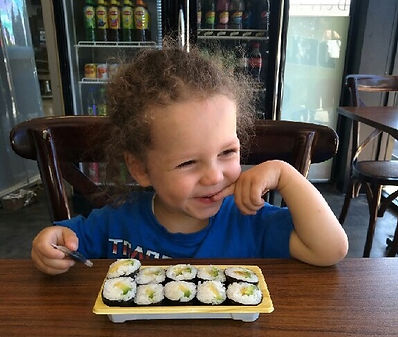 little boy eating sushi