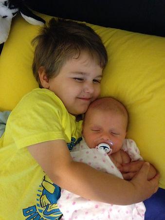brother cuddling new baby