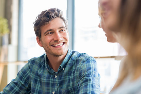 Closeup of cheerful young man in conversation with woman in cafeteria. Happy young couple talking an