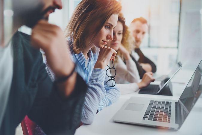 Mulher a segurar óculos, com colegas a trabalhar no computador