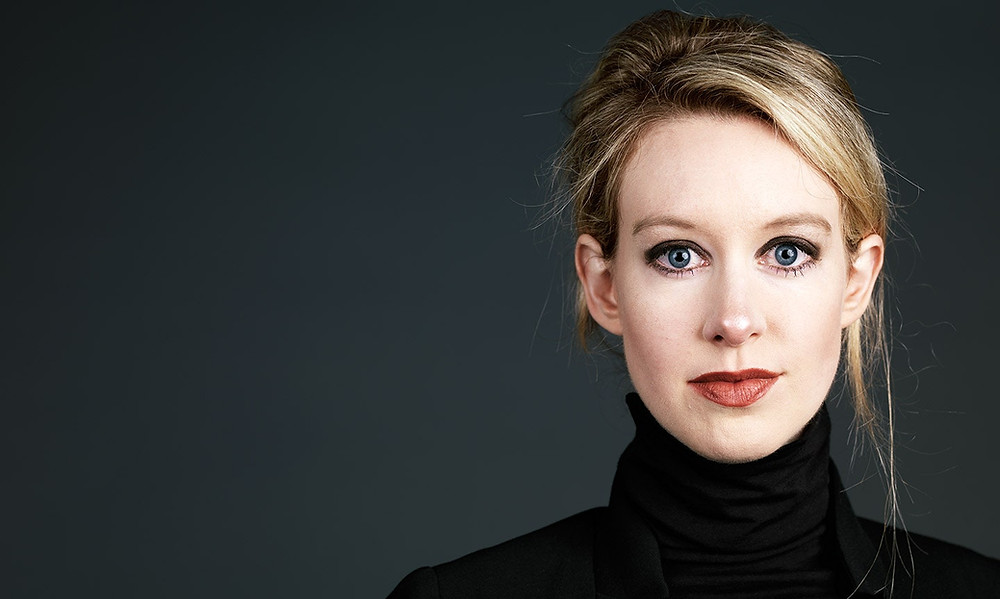 Elizabeth Holmes, a blonde woman with her hair in a messy updo, with blue eyes and red lipstick, wears a black turtleneck wool sweater against a dark grey background.
