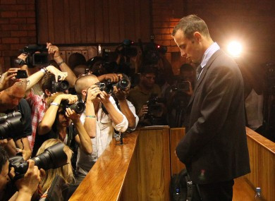 Oscar Pistorius stands with his head bowed, dressed in a dark black suit and blue shirt.  On the left, a crowd of photographers are taking photographs