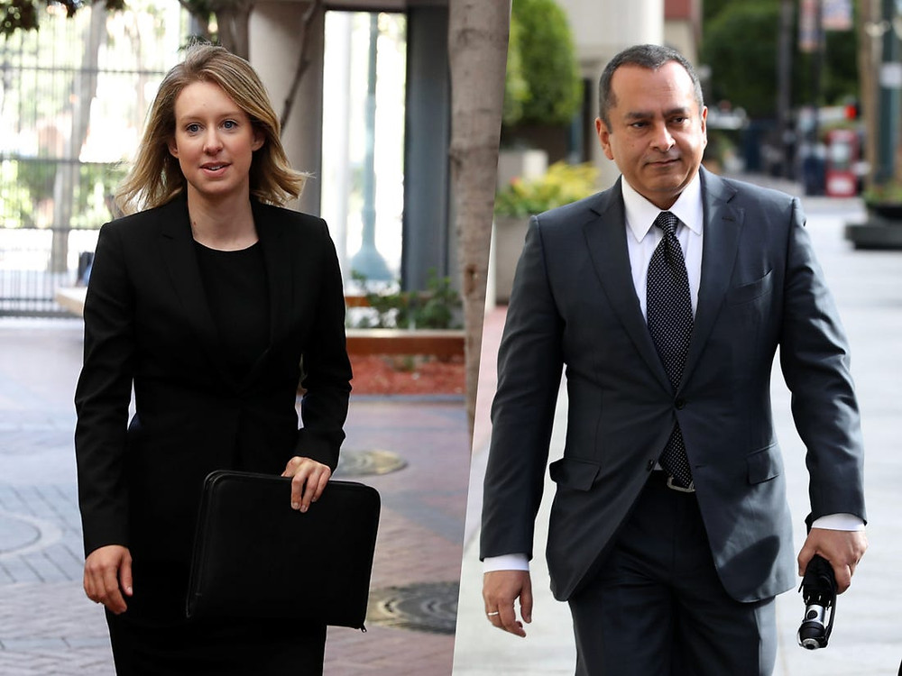 Elizabeth Holmes on the left, dressed in a black suit and carrying a black folder case and on the right, Ramesh Balwani dresssed in a charcoal grey suit, tie and white shirt.