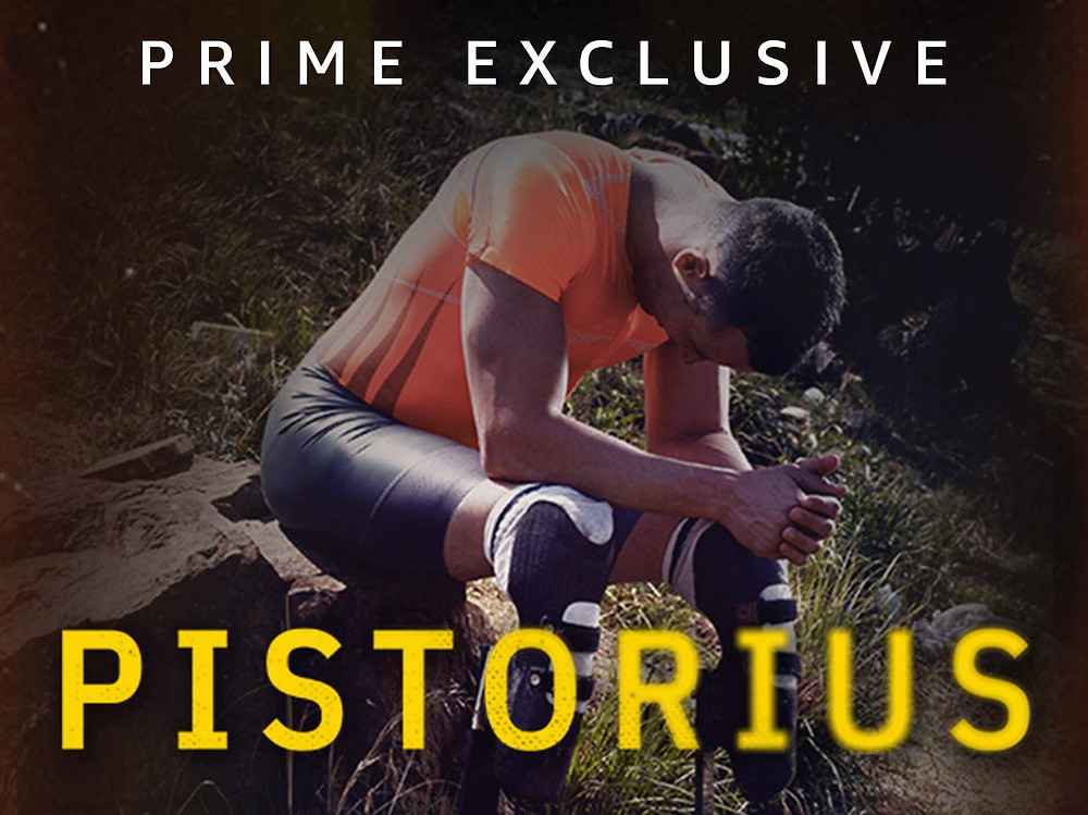 Oscar Pistorius, wearing his prosthetic blades, is sitting on a rock with his head bowed, wearing an orange sports t-shirt and black shorts.  The words 'Prime Exclusive' border the top of the image and the name 'Pistorius' in bold yellow font borders the bottom of the image.