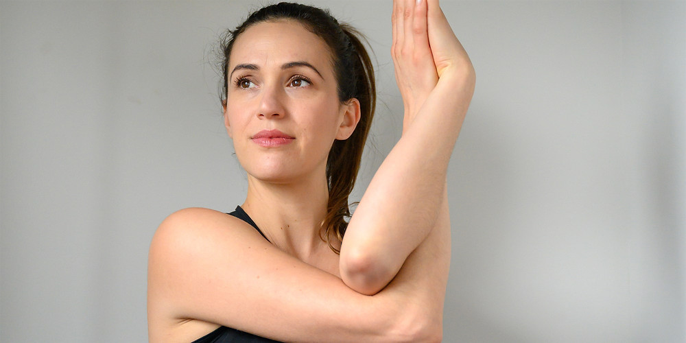 Adriene Mishler, a brunette woman with her hair in a ponytail and wearing a black tank top, folds her arms together in a yoga pose known as the 'eagle' pose.