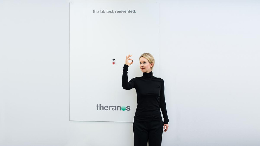 Elizabeth Holmes, a young woman with blonde hair tied back, wearing a black turtleneck jumper and black trousers, holds a tiny red capsule and stands in front of a large with sign with the words 'The lab rest, reinvented' at the top and the 'Theranos' logo on the bottom.