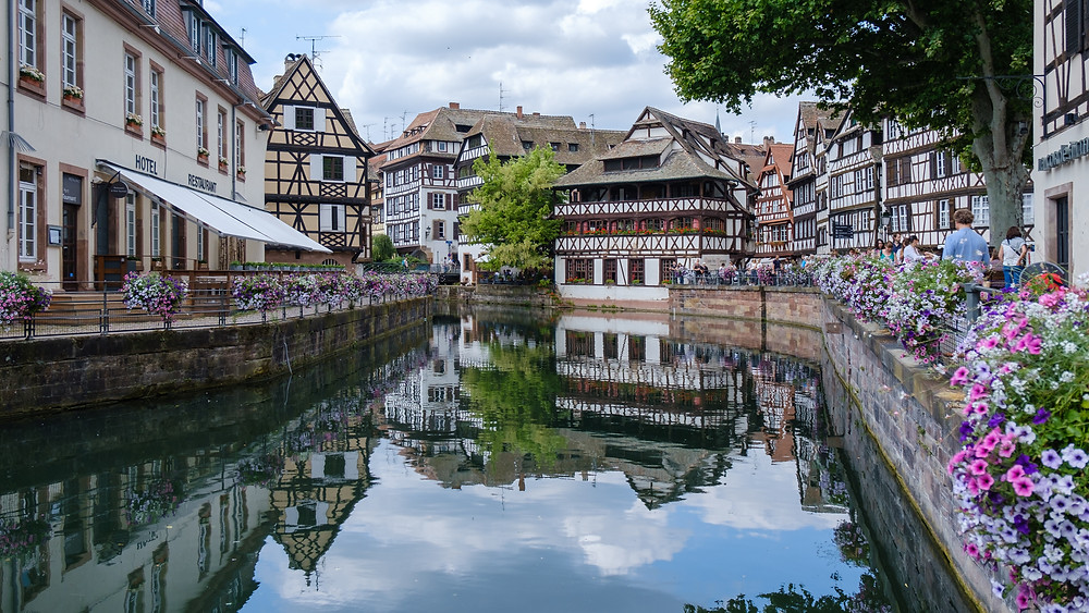A part of the city of Strasbourg, the river winding to the foreground, with flowers on the right hand side and wooden buildings on either side.