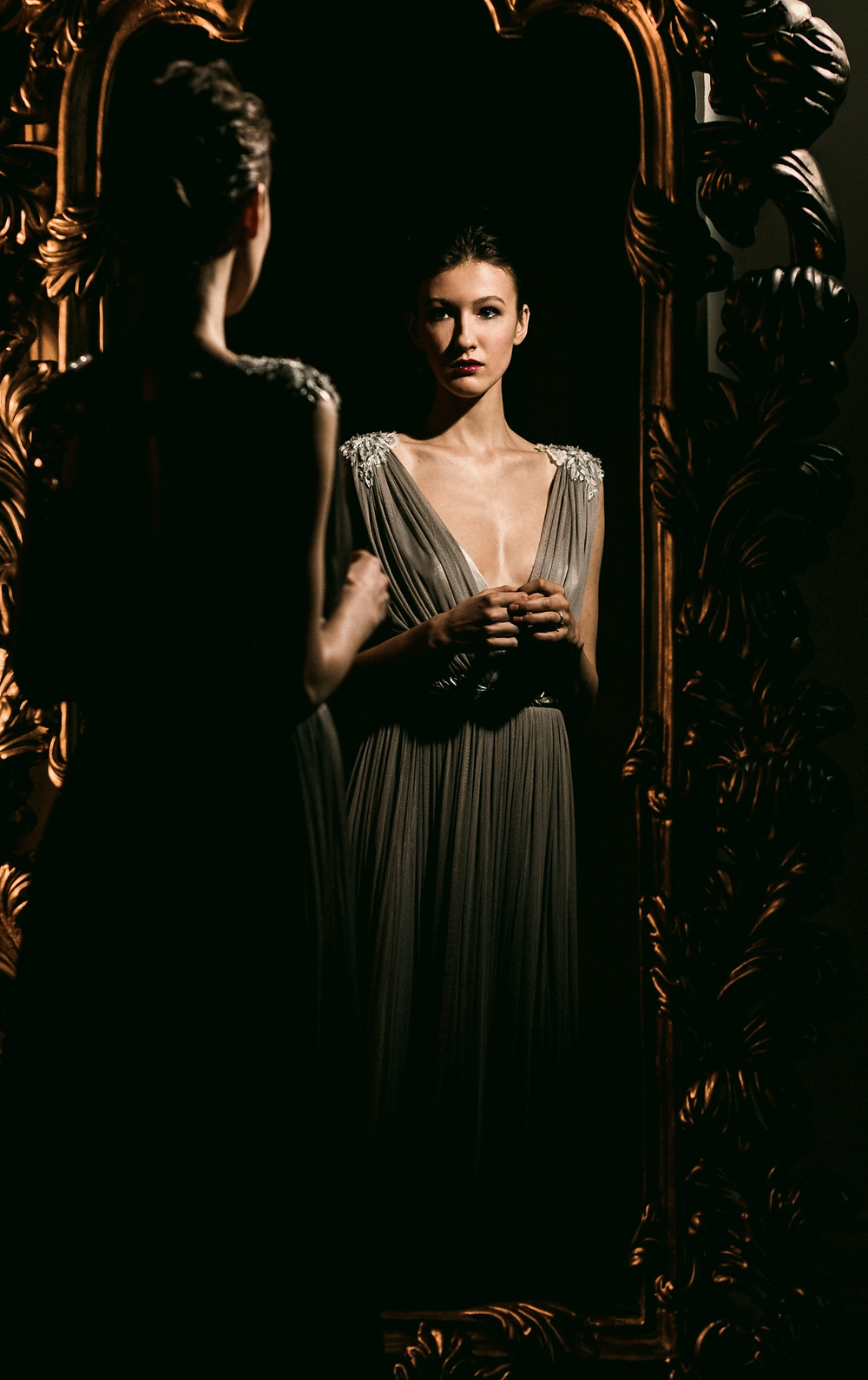 A woman with long dark hair pulled back into a low bun wearing a pale grey ballgown stands in front of an ornate antique brass mirror, staring at her reflection staring back at her.