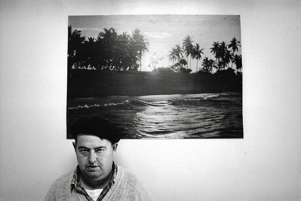 L'hôpital de province, le théatre de l'oubli. Photographies de Jacques Bravo. un homme devant un poster de plage