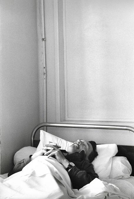 L'hôpital de province, le théatre de l'oubli. Photographies de Jacques Bravo. un homme se repose sur son lit les doigt croisés.