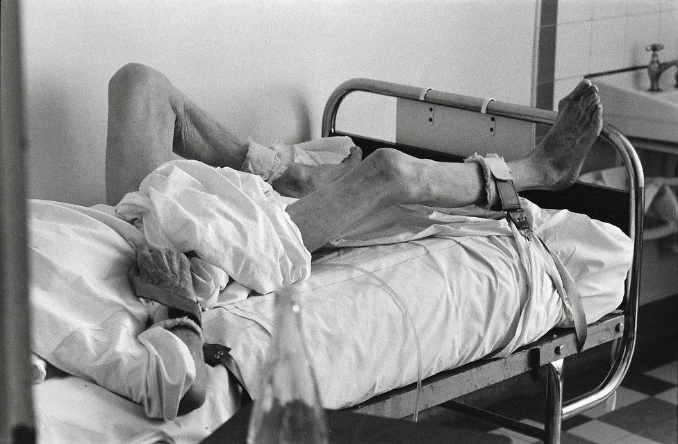 L'hôpital de province, le théatre de l'oubli. Photographies de Jacques Bravo. un homme attaché sur son lit